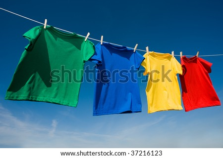 A group of primary colored t-shirts on a clothesline in front of blue sky - stock photo
