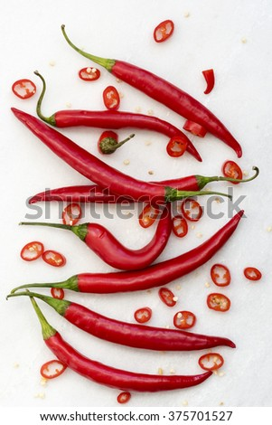 A group of raw red chili peppers and chili pepper slices with seeds on a marble cutting board.  - stock photo