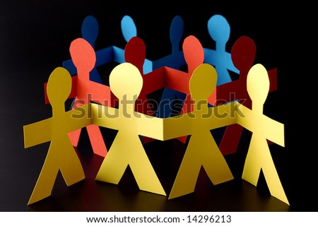 A group of red yellow and blue paper men on black background - stock photo