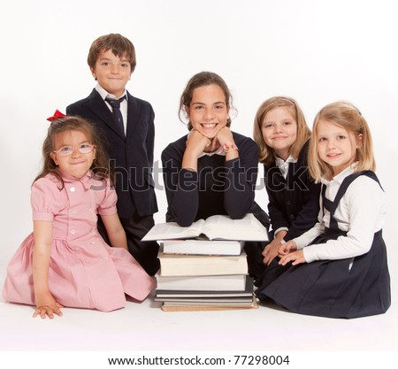 A group of school kids of different ages and a pile of books - stock photo