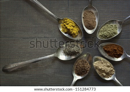 A group of seven antique silver spoons with a different spice in each one on a screen background. - stock photo