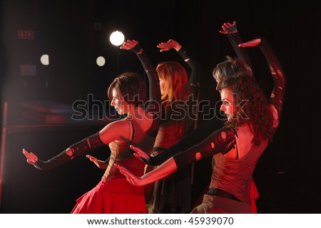 A group of sexy young freestyle dancers on a dark stage with red and blue stage lights - stock photo