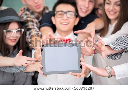 A group of smiling students holding a tablet - stock photo