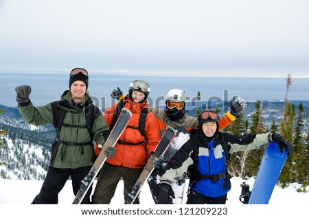 a group of snowboarders and skiers high in mountains - stock photo