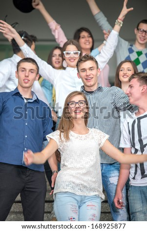 A group of students having fun on school stairs standing - stock photo
