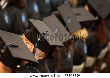 A group of students seated at graduation - stock photo