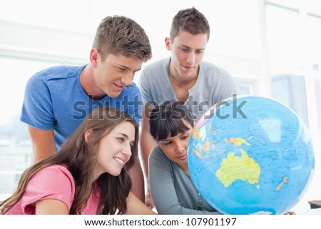 A group of students smile while searching the globe for a country - stock photo