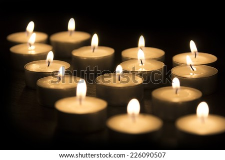 A Group of tea candles burning on a black background - stock photo