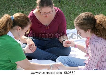 A group of teen girls having a prayer circle outdoors. - stock photo