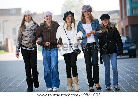 A group of teenage walking towards the camera - stock photo