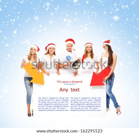 A group of teenagers in Christmas hats pointing on a blank banner and using a megaphone over blue background with the snowflakes - stock photo