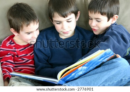 A group of three boys reading a book together - stock photo