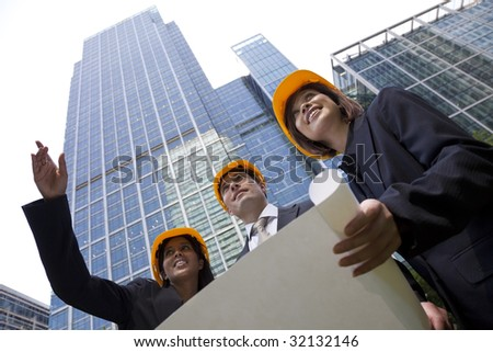 A group of three executives, one man and two women, wearing hard hats review architectural plans in a modern city environment. - stock photo