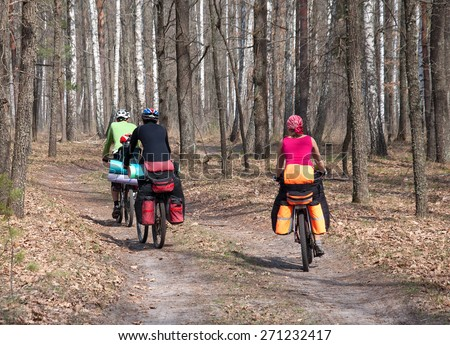 A group of tourists on a mountain bike ride on a forest trail. The rider is back - stock photo