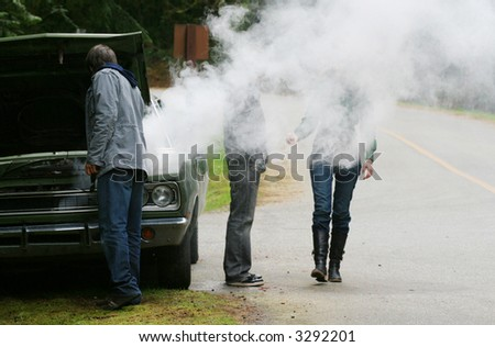 A group of travellers wonders what to do after their car overheats. - stock photo