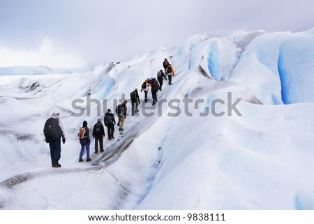 a group of trekking tour on a huge glacier ice in patagonia argentina chile - stock photo