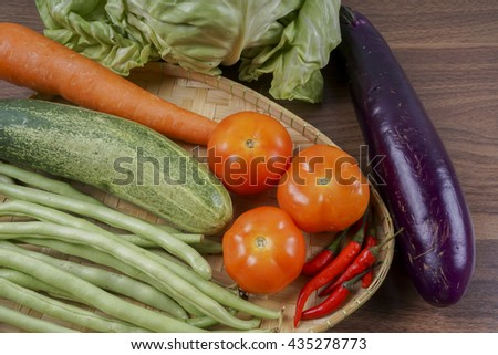 A group of vegetables in a basket.  Cabbage, cucumber,tomato, carrot and beans. Selective focus - stock photo