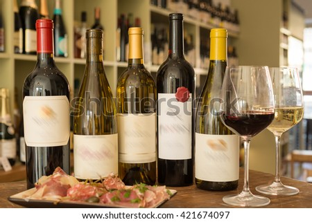 A group of wine bottles with blurred out labels alongside a couple of wineglasses and a deli plate with a wine collection in the background - stock photo