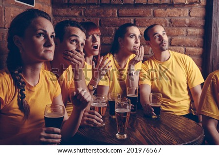 A Group Of Worried  Friends Watching Their Favorite Team At The Bar - stock photo