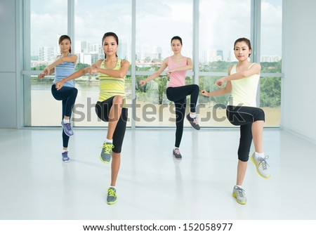 A group of young girls doing aerobics steps in the sport class - stock photo