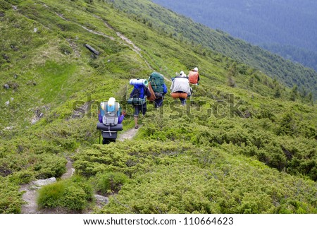 A group of young people go on a mountain path - stock photo