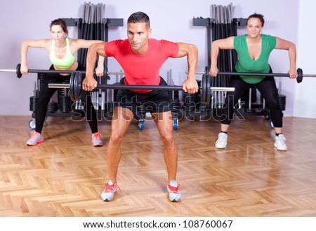 A group of young people in aerobics class doing a dead lift exercise - stock photo