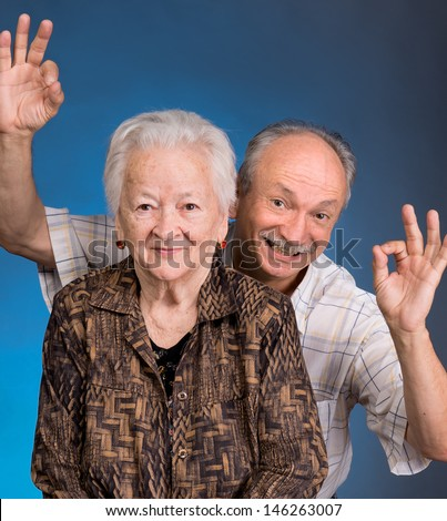 A grown son showing ok with his aging mom on a blue background - stock photo