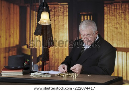A grumpy old miser sitting at his desk counting gold coins by a stack of big bills. - stock photo