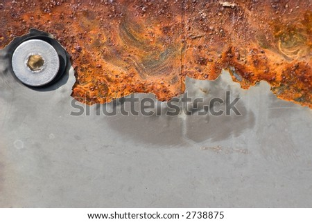 A grunge texture abstract image of rust creating a swirling pattern along with a bolt and and chipped gray paint. - stock photo