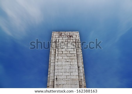 A grungy granite tower against a surreal blue sky with a blank surface for text.  - stock photo