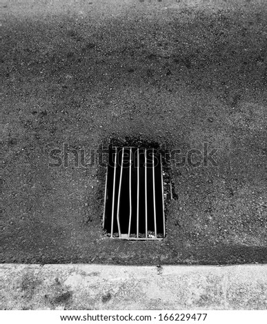 A grungy metal grate of a manhole to an underground drainage system on a asphalt road.  - stock photo