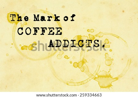 "A grungy paper napkin with coffee mug stains and the message quote ""The mark of coffee addicts"". - stock photo"