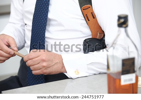 A guard with a cigar in his hand and a gun in shoulder holster - stock photo
