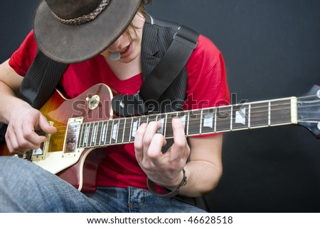 A guitarist improvising with a plectrum in his mouth - stock photo