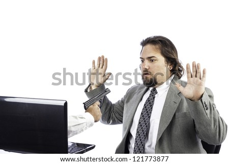 a gun coming out of a computer holding up a business man - stock photo