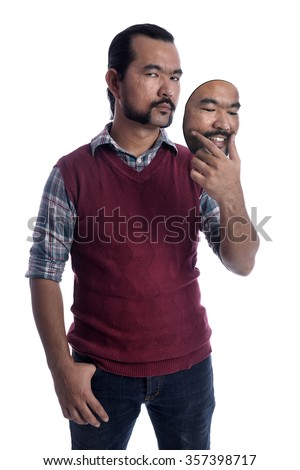 A Guy holding a mask. Hypocritical, insincere, two-faced emotion face. - stock photo