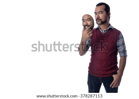 A Guy holding a own mask. Hypocritical, insincere, two-faced emotion face. - stock photo