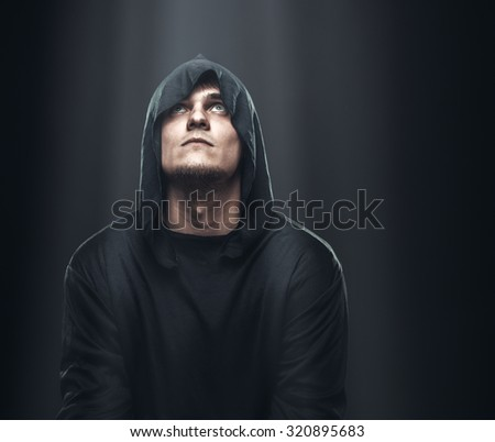 a guy in a black robe standing in the dark under the rays of the moon - stock photo