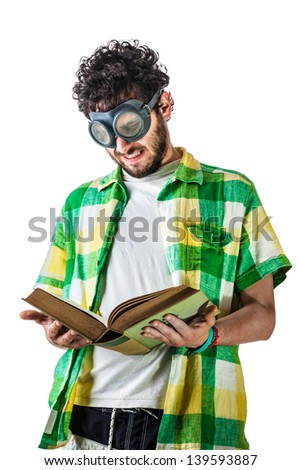 a guy wearing casual clothes and on old pair of goggles over a white bachground and reading an old book - stock photo