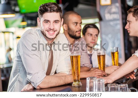 A guy with a beer sitting at the bar and looks at the camera. Three cheerful friends met at the bar and drink a beer while the bartender is standing on the bar. Friends having fun together - stock photo