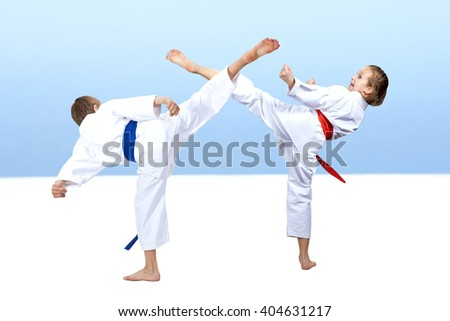 A guy with a blue belt and a girl with a red belt makes a high kick - stock photo