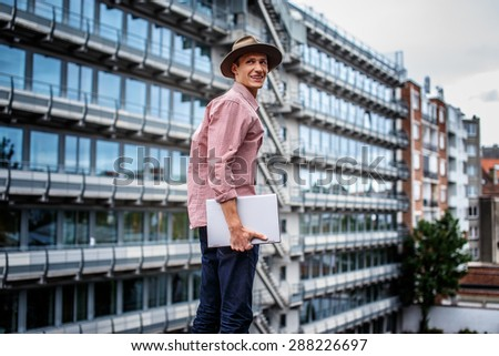 A guy with laptop on multifamily house background. - stock photo