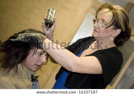 A hairdresser working on a clients hair color at the salon. - stock photo
