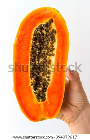 A half ripe papaya with seeds, held in the hand of a young woman, isolated on white. - stock photo