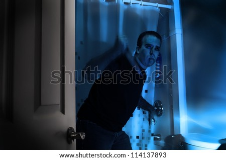 A halloween killer is sneaking around in a bathroom, about to murder someone in the shower. - stock photo