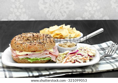A ham and swiss cheese sandwich on a whole grain multi seed bagel. Sides of spicy mustard, cole slaw and chips.  Copy space. - stock photo