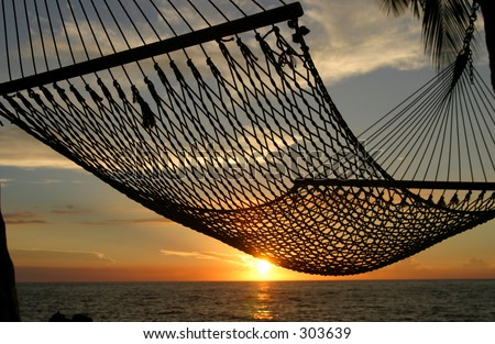 A hammock on the Big Island of Hawaii with the sunset in the background. - stock photo