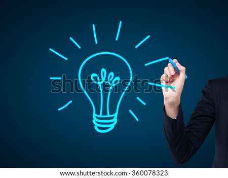 A hand drawing a huge shining blue bulb with a light blue marker on the dark blue background. Concept of a new idea. - stock photo