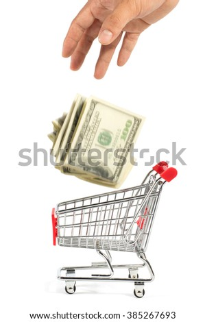 A hand dropping some one hundred US dollar bills into a shopping cart, isolated on white background.  - stock photo