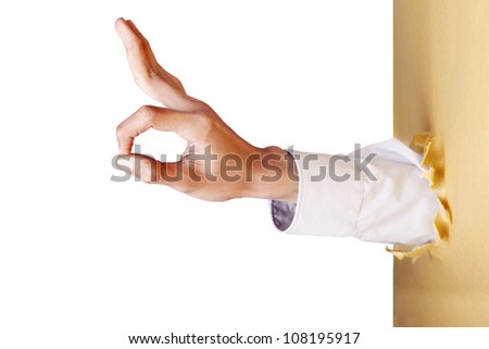 A hand gesture giving ok signal breaking through a paper wall - stock photo